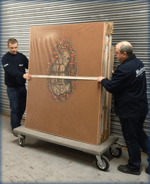 2 men transporting large artwork