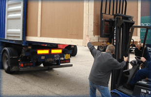 Forklift loading large wooden box onto trcuk